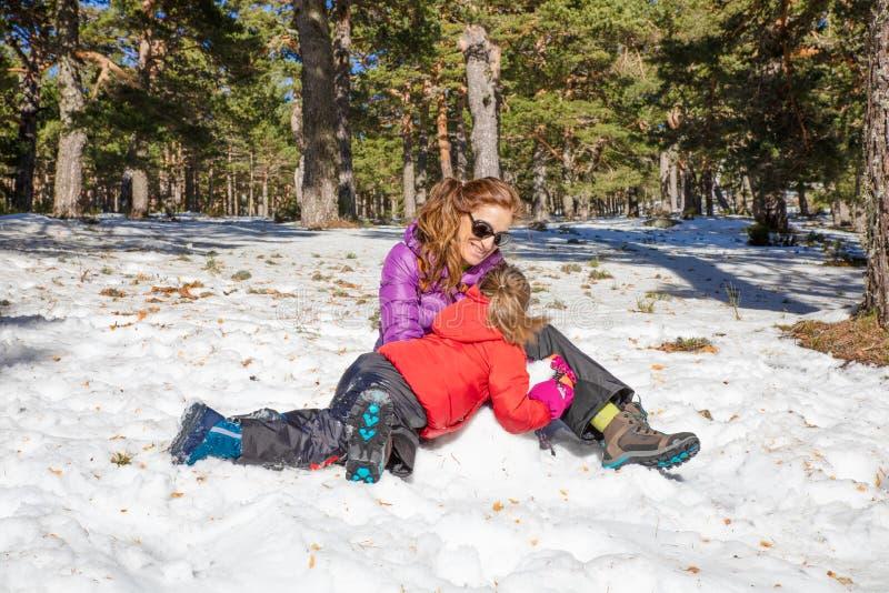 Frau und ihre kleine Tochter, die auf dem Schnee lachen lizenzfreie stockfotos