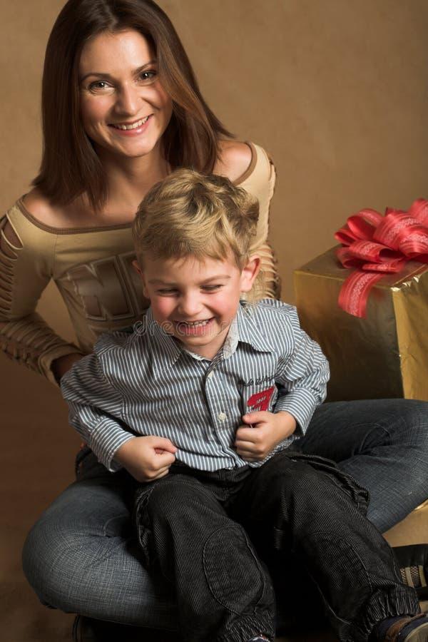 Frau und Junge, die Weihnachtsgeschenke überprüfen stockbild