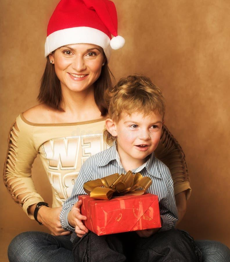 Frau und Junge, die Weihnachtsgeschenke überprüfen lizenzfreies stockbild