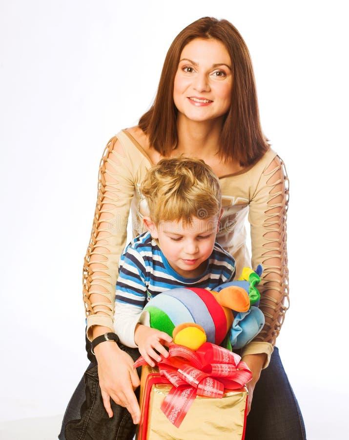 Frau und Junge, die Weihnachtsgeschenke überprüfen lizenzfreie stockfotografie