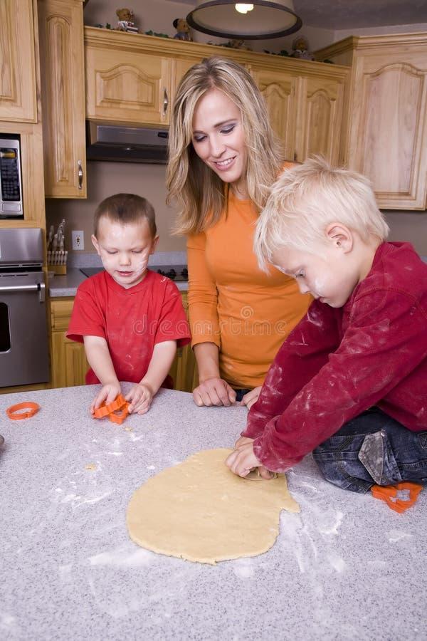 Frau und Jungen, die Plätzchen bilden lizenzfreies stockfoto