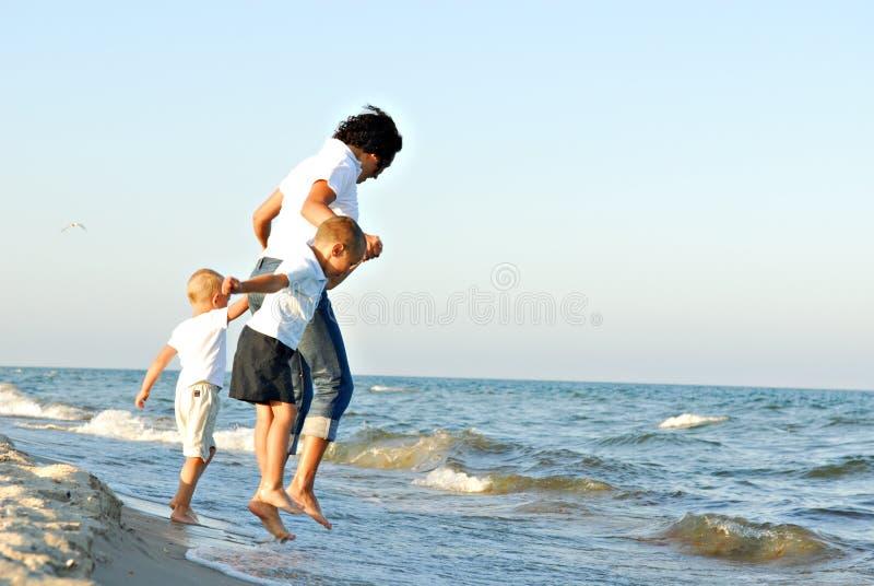 Frau und Jungen, die Wellen springen stockfotografie