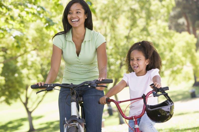 Frau und junges Mädchen auf Fahrrädern draußen lächelnd lizenzfreies stockfoto