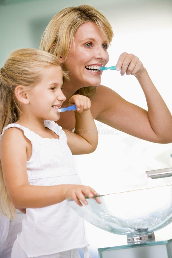 Frau und junges Mädchen in auftragenden Zähnen des Badezimmers stockbilder
