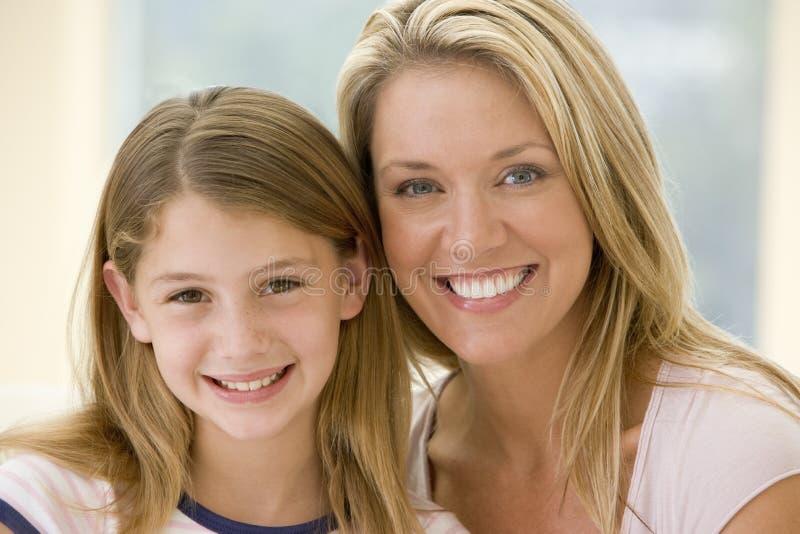 Frau und junges Mädchen beim Wohnzimmerlächeln lizenzfreies stockfoto