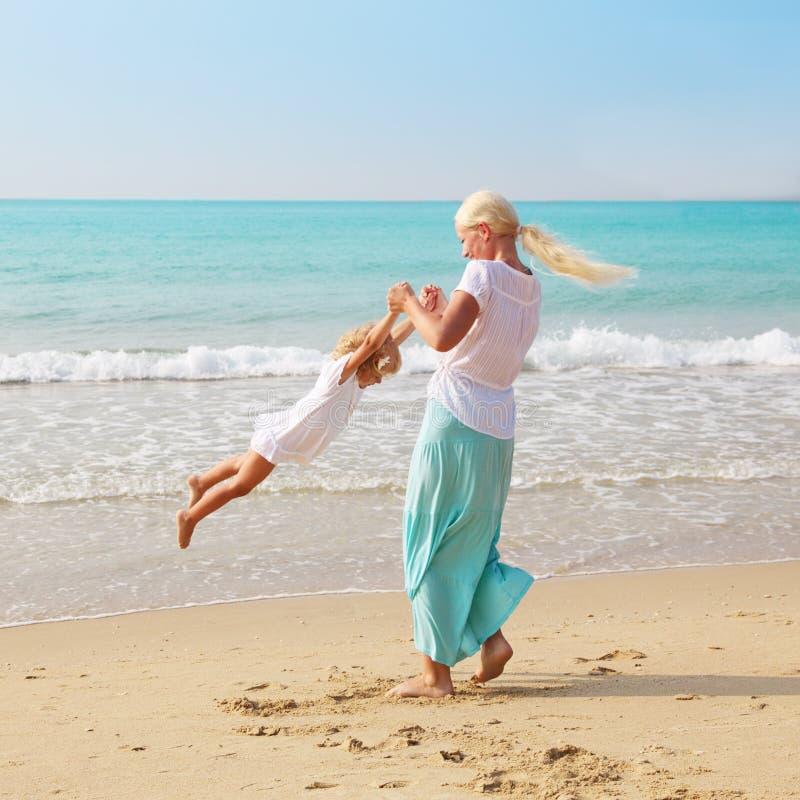 Frau und Kind auf dem Strand stockbilder
