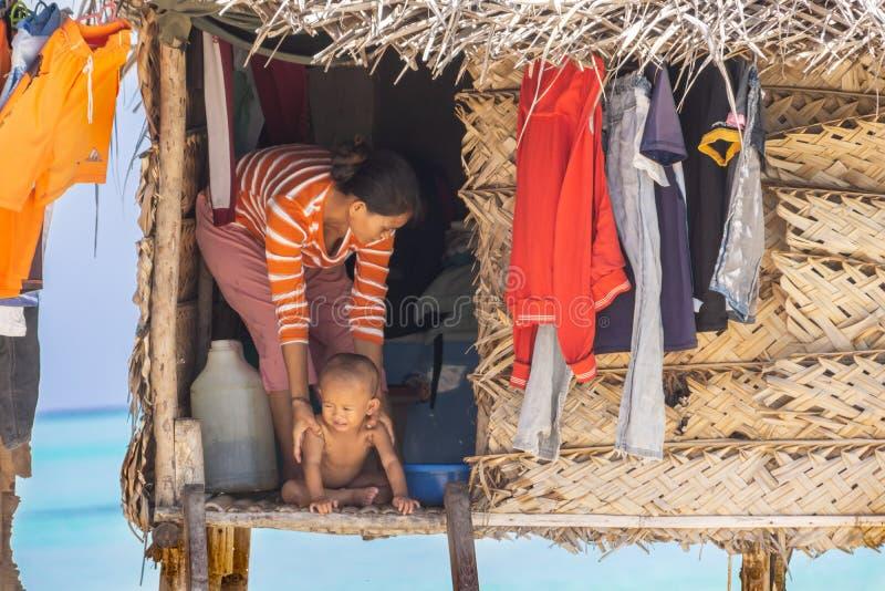 Frau und Kind im Eingang des traditionellen Hauses stockfotos