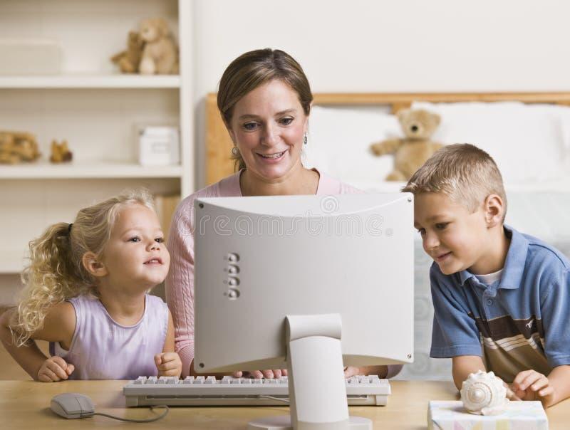 Frau und Kinder, die auf Computer spielen lizenzfreies stockfoto