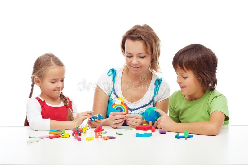 Frau und Kinder, die mit buntem Lehm spielen stockfoto
