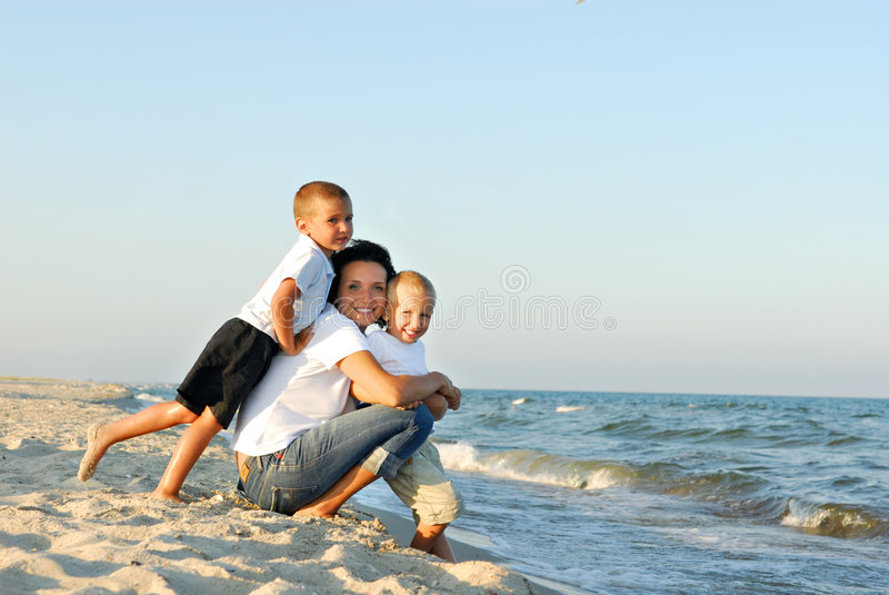 Frau und Kinder am Strand stockbild