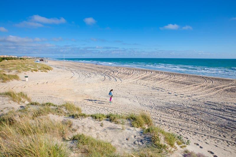 Frau und kleines Mädchen, die auf Sand von La Barrosa-Strand in Cad gehen lizenzfreie stockfotos