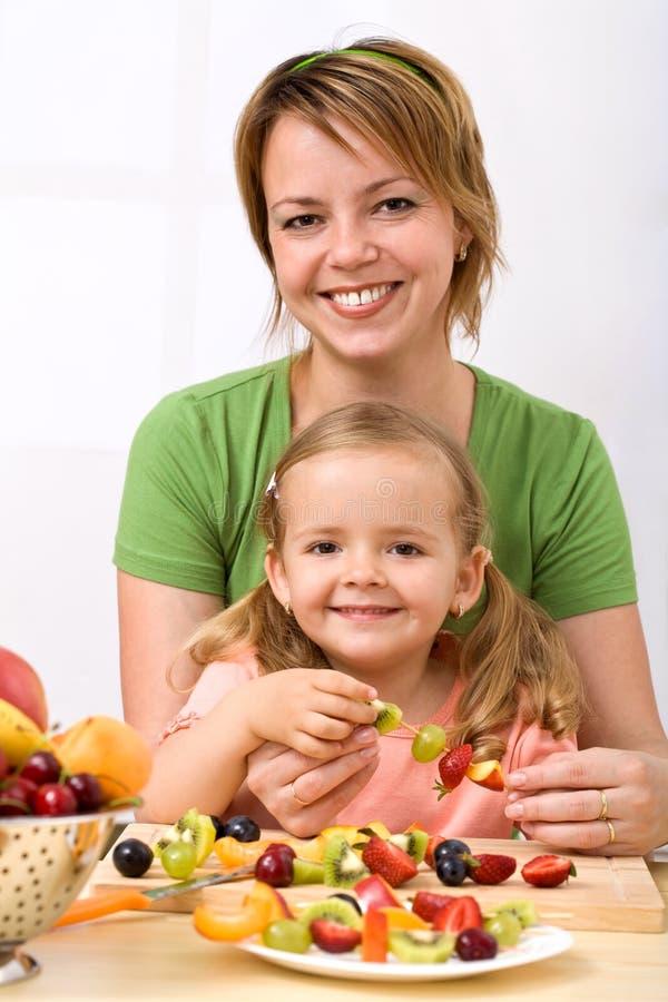 Frau und kleines Mädchen, die Frucht kebab bilden lizenzfreie stockfotografie