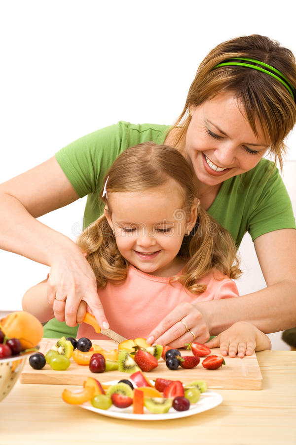 Frau und kleines Mädchen, die Fruchtsalat zubereiten stockbilder