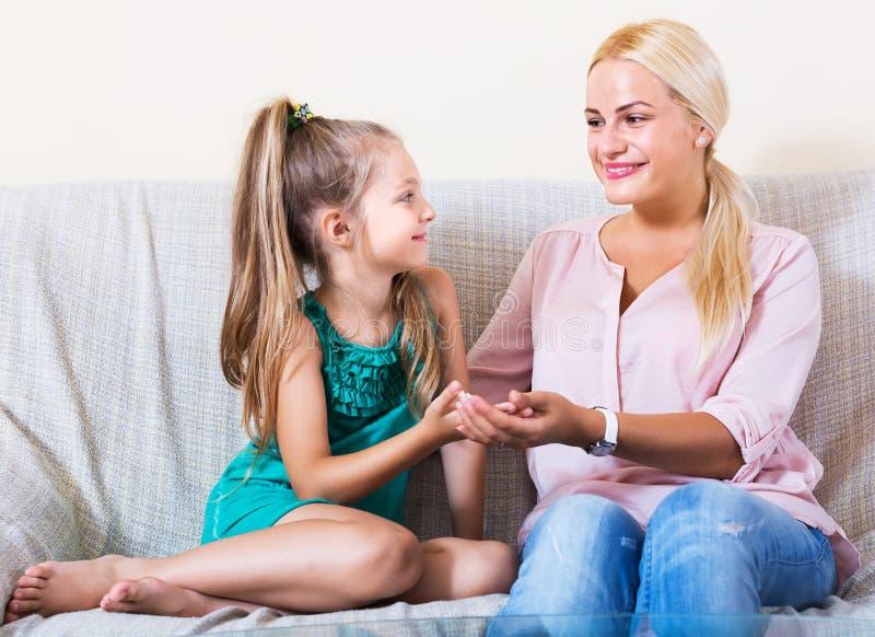 Frau und kleines Mädchen, die Gespräch haben stockbild