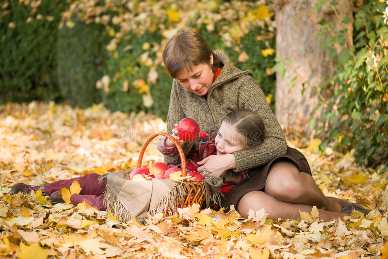 Frau und kleines Mädchen im Herbst parken mit Apfelkorb lizenzfreie stockbilder
