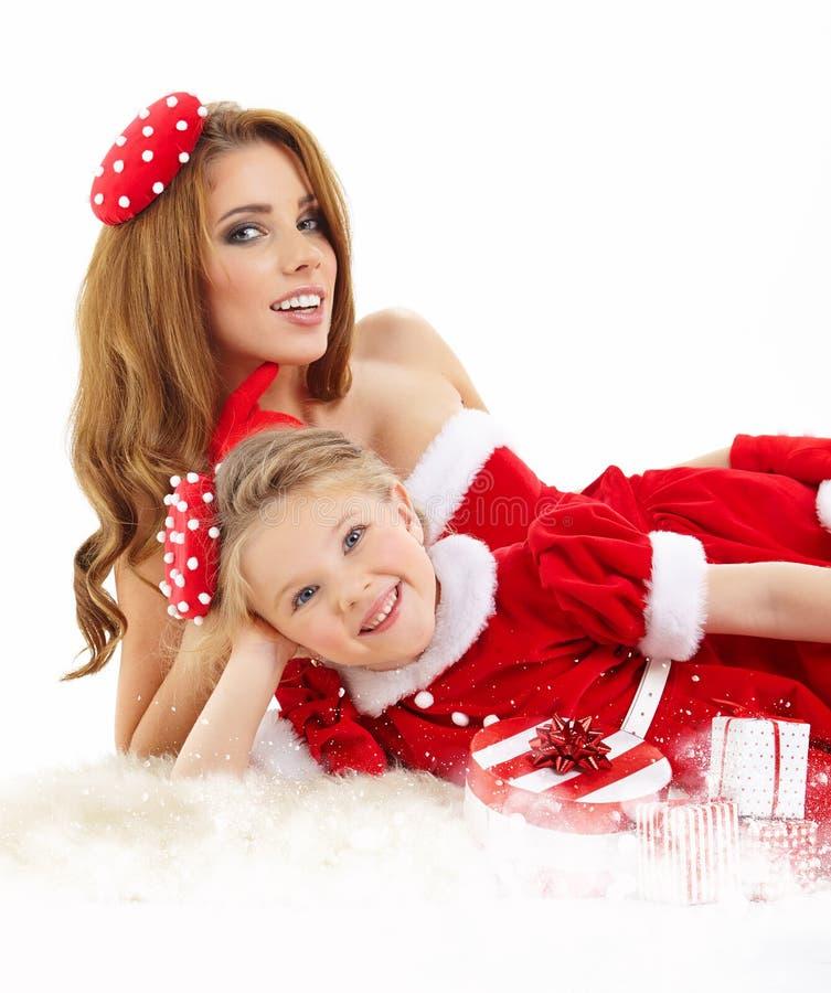 Frau und kleines Mädchen kleideten im Kostüm Weihnachtsmann an lizenzfreie stockbilder