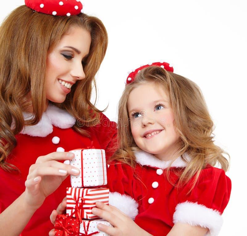 Frau und kleines Mädchen kleideten im Kostüm Weihnachtsmann an stockbilder