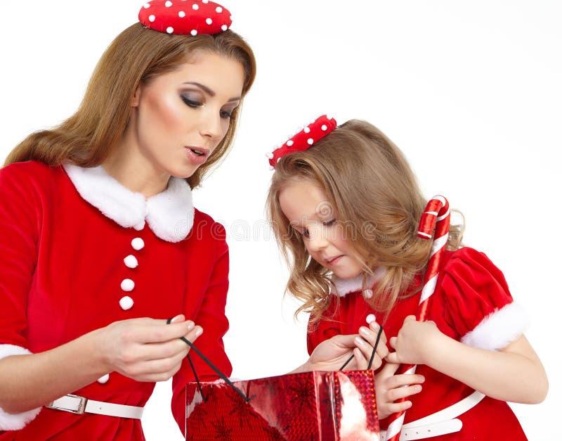 Frau und kleines Mädchen kleideten im Kostüm Weihnachtsmann an stockfotografie