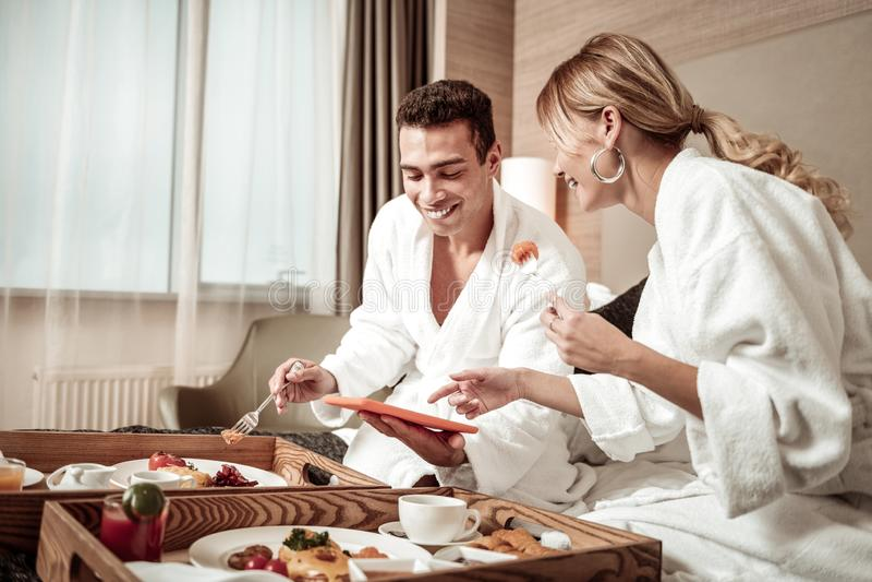 Frau und lachender aufpassender lustiger Film und Essen des Ehemanns stockfoto