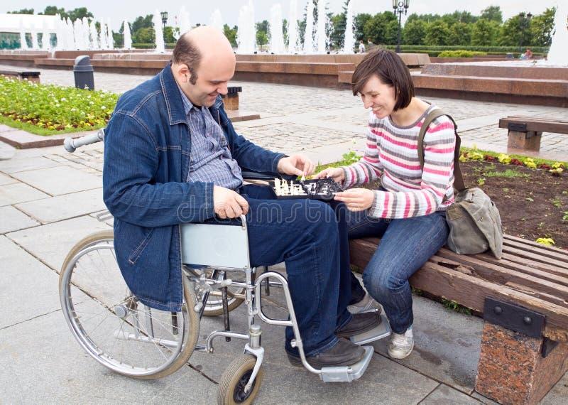 Frau und Mann auf einem Rollstuhl stockfotografie