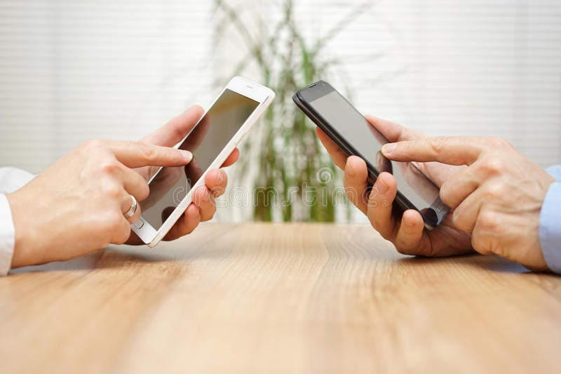 Frau und Mann, der zusammen Anwendungen am intelligenten Mobiltelefon verwendet stockbilder
