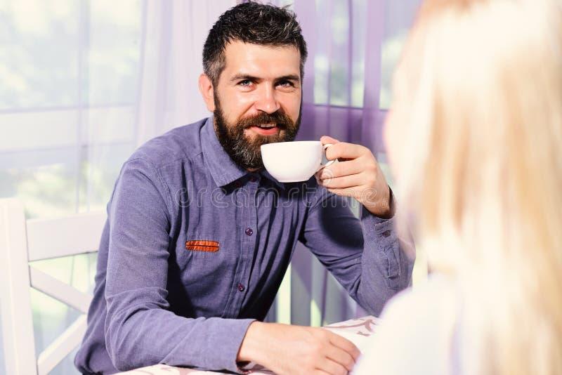 Frau und Mann mit glücklichem Gesicht haben ein Datum Paar in der Liebe hält Tasse Kaffees bei Tisch stockbild