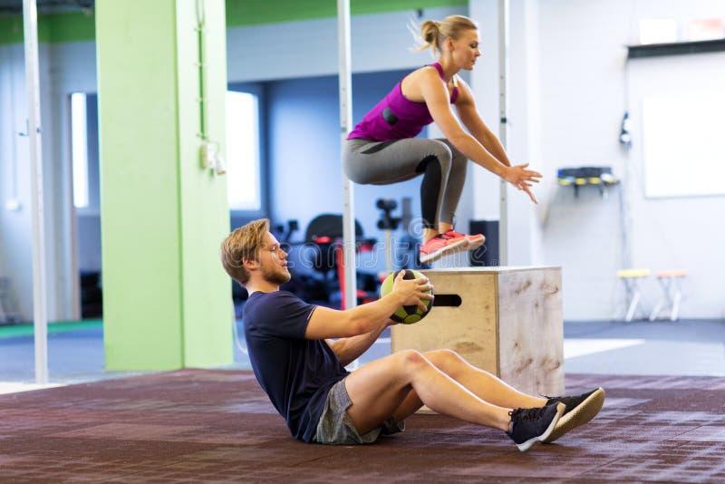 Frau und Mann mit Medizinball trainierend in der Turnhalle lizenzfreies stockbild