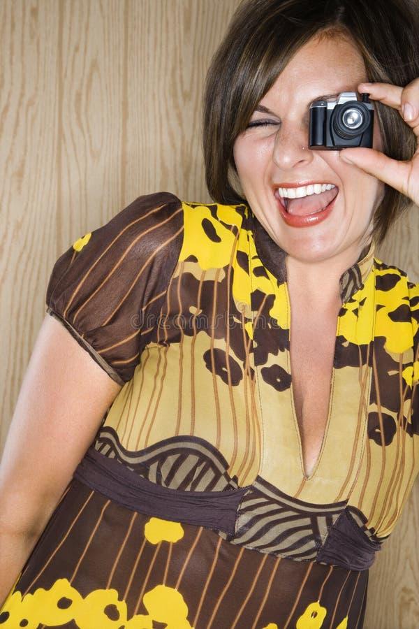 Frau und Miniaturkamera. stockbilder
