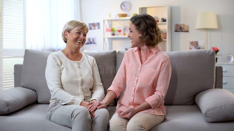 Frau und Patin, die zusammen, Händchenhalten, Familienkommunikation, Spaß lachen stockfotografie