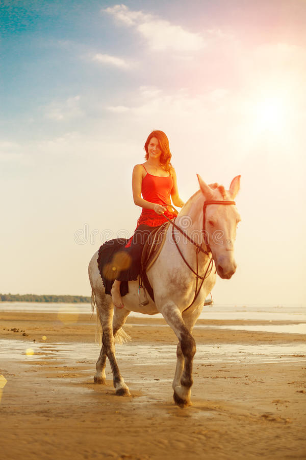 Frau und Pferd auf dem Hintergrund des Himmels und des Wassers Mädchen vorbildliches O lizenzfreie stockbilder