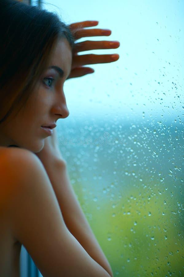 Frau und regnerisches Fenster lizenzfreies stockbild