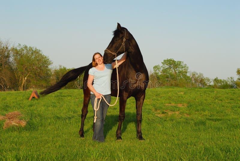 Frau und schwarzes Pferd lizenzfreie stockfotos