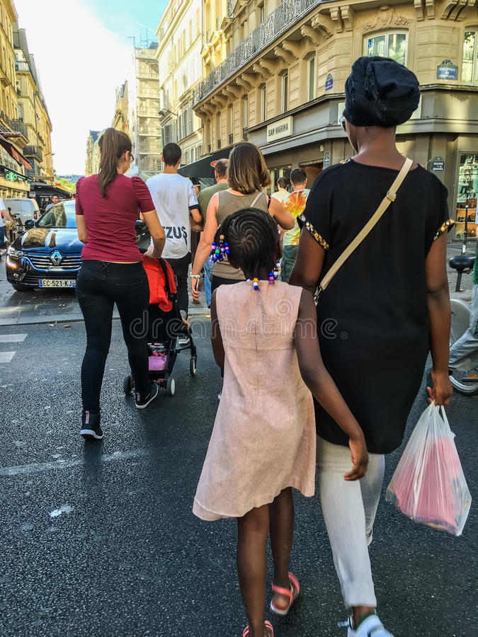 Frau und Tochter schlendern hinunter Paris-Straße unter verschiedener Menge lizenzfreie stockfotografie