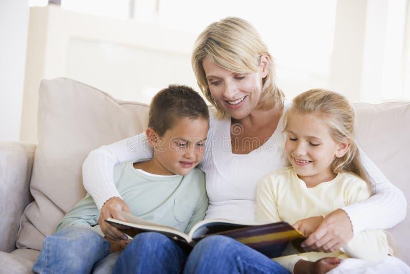 Frau und zwei Kinder, die im Wohnzimmer sitzen stockfotos