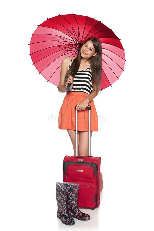Frau unter dem Regenschirm, der mit Koffer und Gummistiefeln staning ist lizenzfreies stockfoto