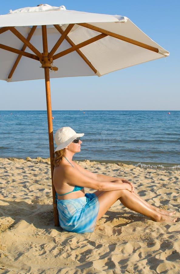 Frau unter einem Solarregenschirm stockbilder
