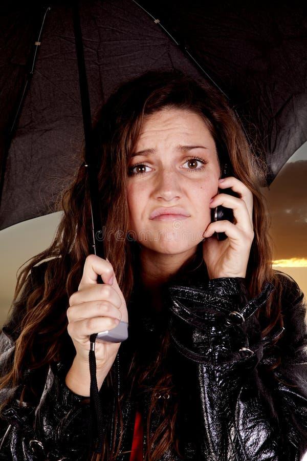Frau unter Regenschirm am Telefon stockfotos