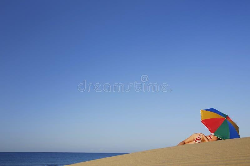 Frau unter Sonnenschirm lizenzfreies stockbild