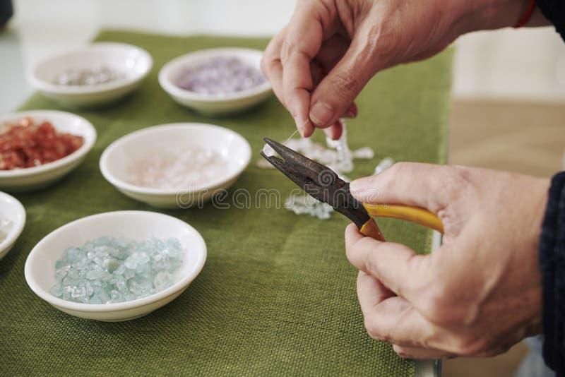 Frau unter Verwendung der Zangen beim Bördeln stockfotos
