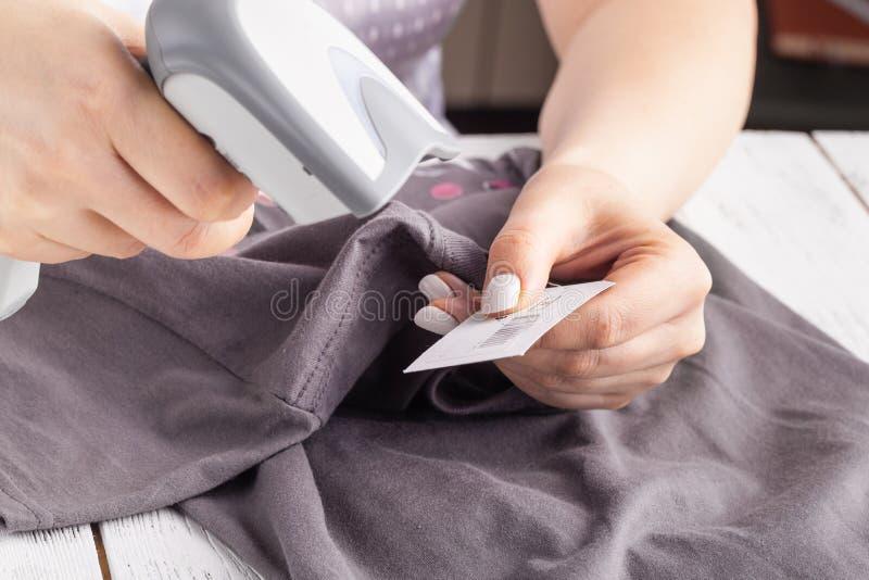 Frau unter Verwendung des Barcode-Scanners auf Kleidung lizenzfreie stockfotos