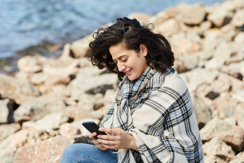 Frau unter Verwendung Smartphones durch See lizenzfreie stockbilder