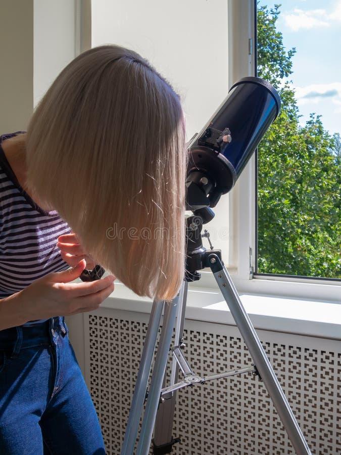 Frau untersucht durch ein Fenster ein Teleskop lizenzfreies stockfoto