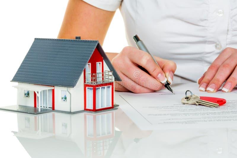 Frau unterzeichnet Kaufvereinbarung für Haus lizenzfreie stockfotografie