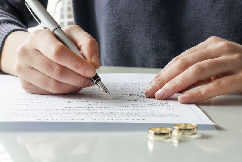 Frau unterzeichnet Scheidungsverordnungsform mit Ring lizenzfreie stockbilder