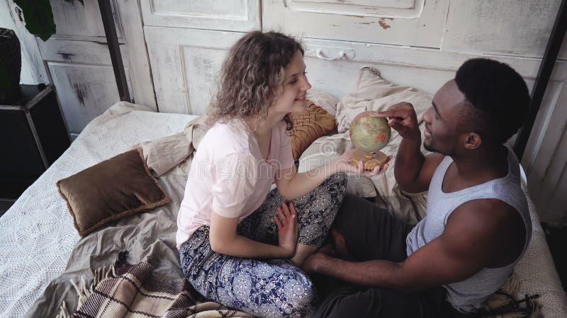 Frau verdreht die Kugel, Mann-Auswahl der Standort zum Reisen Gemischtrassige Paare in den Pyjamas freuen sich, umarmen und küsse stockfoto