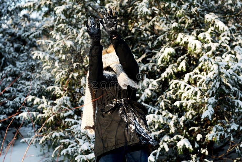 Frau verteidigt sich Schneeballkampf spielend stockfotos