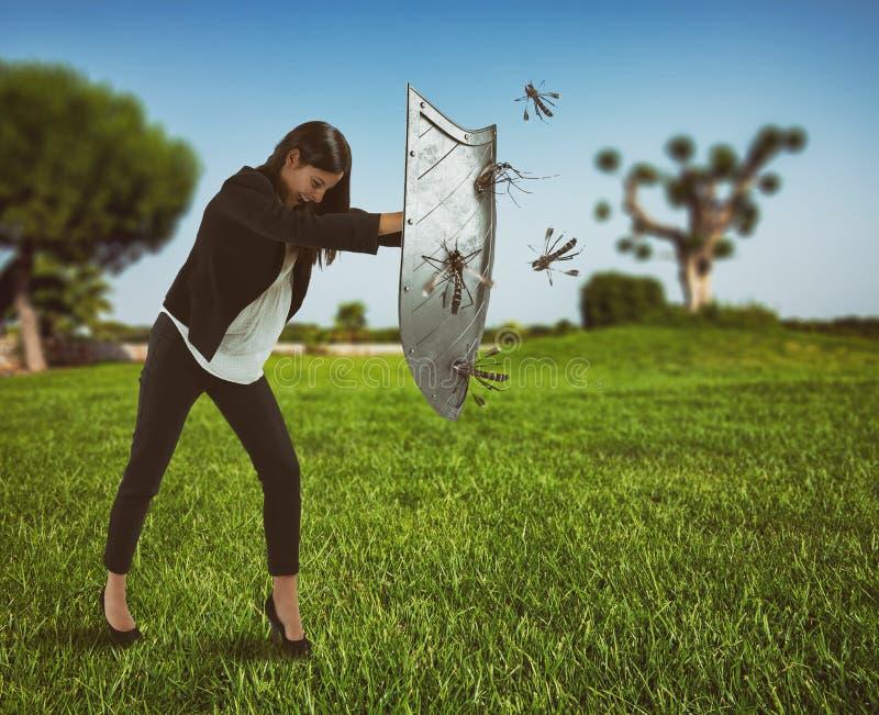 Frau verteidigt sich vom Angriff von Moskitos mit einem Schild stockbilder