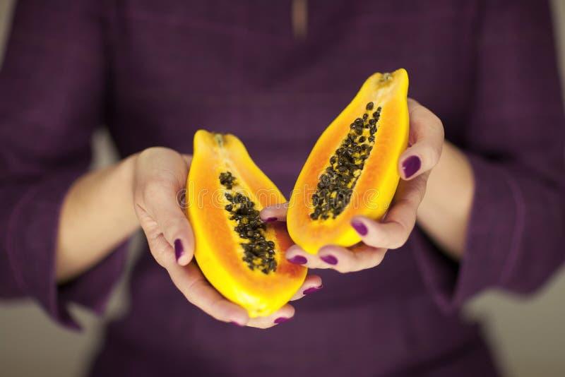 Frau in violett 50 ` s Kleid übergibt das Halten einiger Papayas stockbild