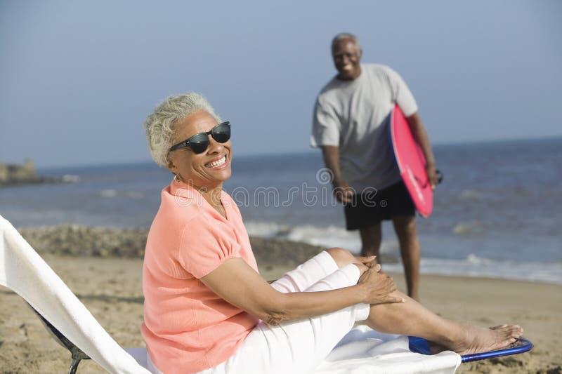 Frau von mittlerem Alter, die auf einem deckchair auf einem Strand sitzt stockfotografie