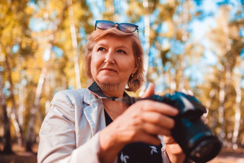 Frau von mittlerem Alter, die Bilder auf Kamera in der Herbstwaldälteren Frau geht und genießt Hobby überprüft stockfotografie